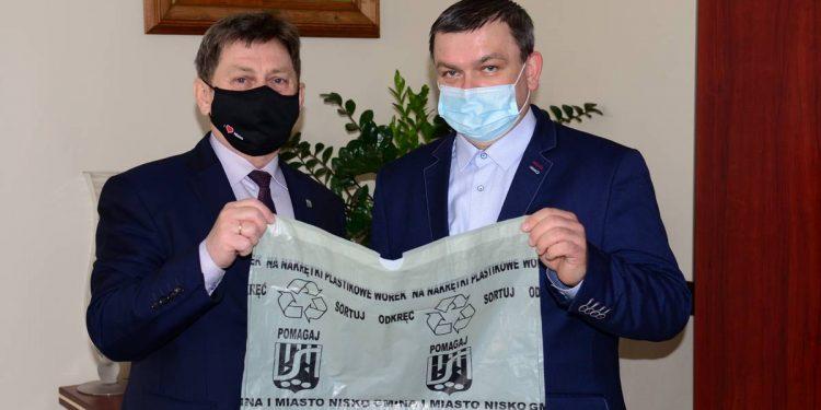 Burmistrz Waldemar Ślusarczyk i prezes MZK Nisko Dariusz Dul prezentują worek, do którego będzie można zbierać nakrętki